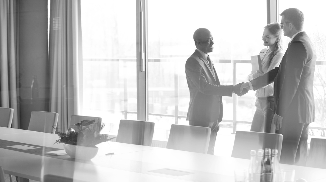 three people in a business conference room shaking hands